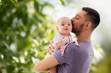family, parenthood and people concept - happy father kissing little baby daughter over green natural background