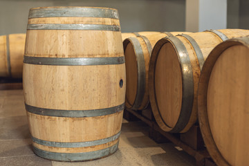 Wine oak barrels in which red wine is aged in the cellar of the winery. Concept of the production of wine