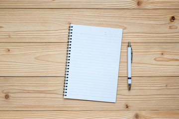 blank notebook with pen on wooden background. top view and copy space for your text