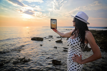 Good Looking Woman Taking Photo Of Beautiful Twilight Sky With Her Tablet On The Rocky Seashore, Side View
