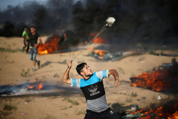 Palestinian hurls stones at Israeli troops during a protest at the Israel-Gaza border fence east of Gaza City