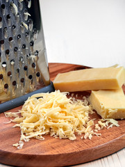 Cheese, grated on a coarse grater, set on a brown wooden board