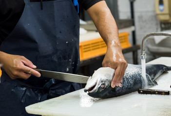 man filleting salmon on white cutting board, The chef cutting fish at table