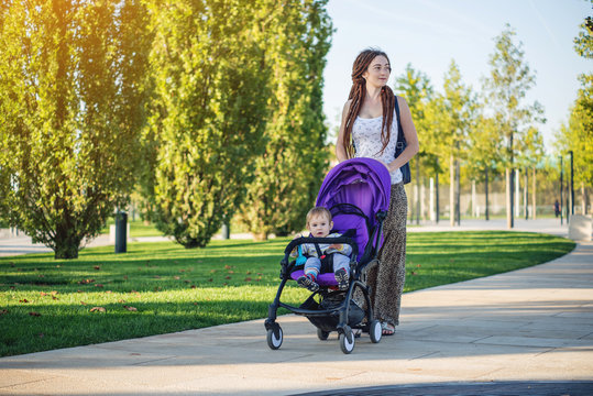 Young modern mom with baby son in stroller walking in Sunny Park. Concept of the joy of motherhood and autumn mood