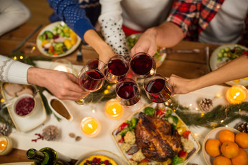 holidays and celebration concept - close up of friends having christmas dinner at home, drinking red wine and clinking glasses