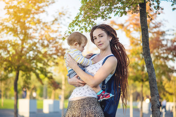 Young modern happy mom with baby son walking in Sunny Park. Concept motherhood and autumn mood