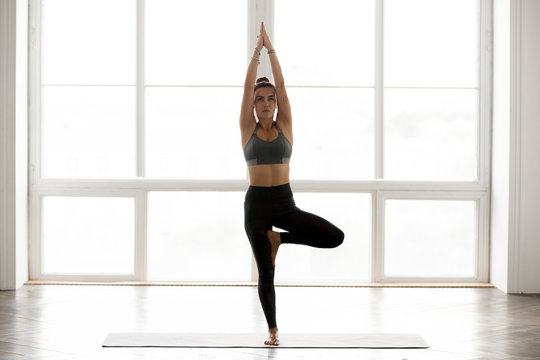 Young sporty attractive woman practicing yoga, doing Vrksasana exercise, Tree pose, working out, wearing sportswear, grey pants, top, indoor full length, at yoga studio