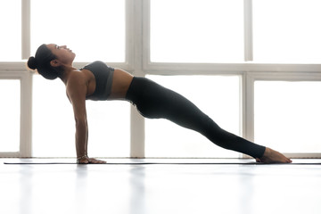 Young sporty attractive woman practicing yoga, doing Purvottanasana exercise, Upward Plank pose, working out, wearing sportswear, grey pants, top, indoor full length, at yoga studio