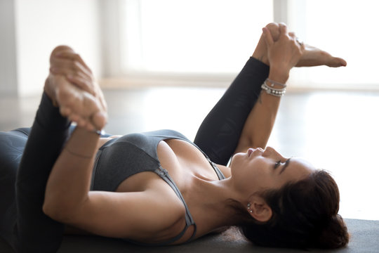 Young sporty attractive woman practicing yoga, doing Happy Baby exercise, Ananda Balasana pose, working out, wearing sportswear, grey pants, top, indoor close up, at yoga studio