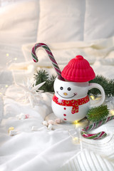 cozy soft blanket with a cup in the form of a snowman with Christmas candies on the bed with flashlights. Cristmas concept lazy morning, warm winter mood