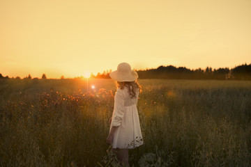 Beautiful girl in a hat at sunset.