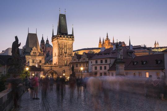Charles Bridge, Lesser Towers, and Prague Castle at night with blurred pedestrians, Prague, Czech Republic
