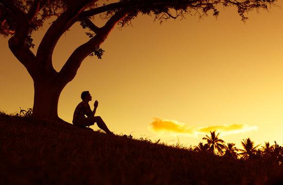 Silhouette of man praying outdoors.