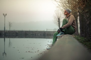 Young stylish guy sitting on the waterfront near the lake. Young guy on the background of the autumn park.