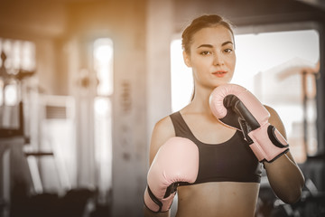 Fit beautiful woman boxer hitting a huge punching bag exercise class in a gym. Boxer woman making direct hit dynamic movement. Healthy, sports, lifestyle, Fitness, workout concept. With copy space.