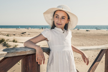 girl with white hat resting on a wooden railing on the beach