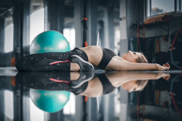 Young attractive woman fitness exercise workout in gym. Woman stretching the muscles and relaxing after exercise at fitness gym club.