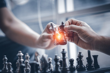 Business competition strategy and business success concept. Hand of two businessman moving for fighting dark king chess piece on chessboard game.