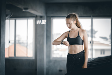 Fit young woman caucasian running on machine treadmill and looking smart watch workout in gym.