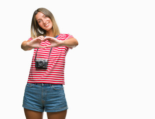 Young beautiful woman taking pictures using vintage photo camera over isolated background smiling in love showing heart symbol and shape with hands. Romantic concept.