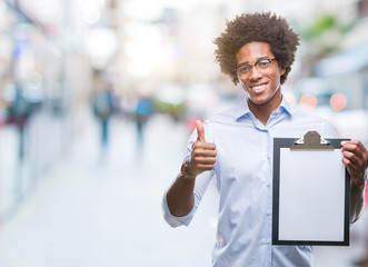 Afro american man holding clipboard over isolated background happy with big smile doing ok sign, thumb up with fingers, excellent sign