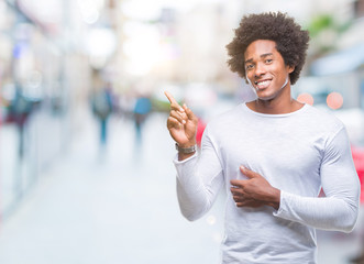Afro american man over isolated background with a big smile on face, pointing with hand and finger to the side looking at the camera.