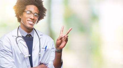 Afro american doctor man over isolated background smiling with happy face winking at the camera doing victory sign. Number two.