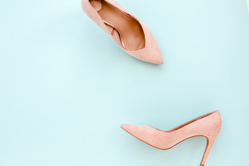 Wall Mural - Pastel pink women high heel shoes on blue background. Flat lay, top view trendy fashion feminine background. Beauty blog concept. Fashion blog look.