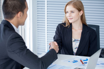 business woman shaking hands with businessman in office