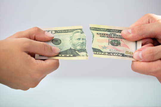 Two Businesspeople Holding Torn Banknote