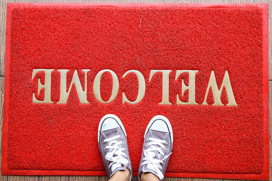 A pair of trainers on red welcome mat texture background.