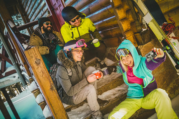 Friends drinking hot tea on snowy mountain