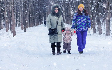 family with kid walk in winter park snowy