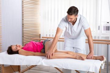 Therapist Massaging Woman's Leg