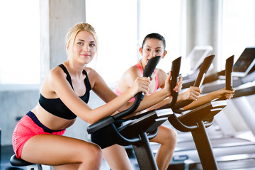 Portrait of a beautiful woman Caucasian. Smiling happily Put on sportswear Exercise by playing an electric Spin bike in the gym. The sport will make you feel refreshed. And have a healthy body.