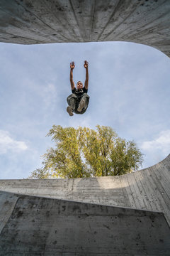 Young athletic man performing a parkour and freerunning jump on a high wall