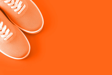 Bright orange sneakers on an orange background.