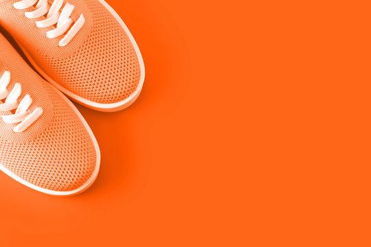 Bright orange sneakers on an orange background.