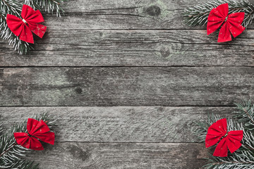 Four fir branches with red bows, and xmas handmade toys on wooden gray background, with space for text, Christmas greeting card