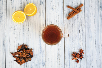 Cup of tea, lemon, cinnamon, cloves, dried tea leaves