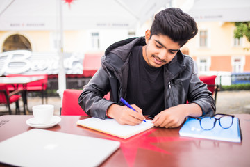 Young stylish indian man city in cafe in city writing notes in book