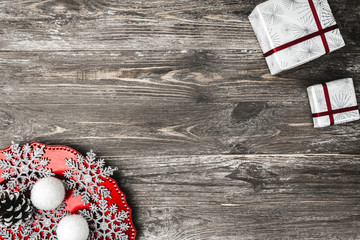 Upper, top view, of Christmas presents and a plate with homemade decorative snowflakes on a wooden brown rustic background, with space for text writing.