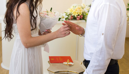 The bride puts the ring on the groom