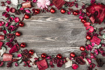 Upper, top, view from above, of decorative dried, painted flower petals, bark, in Christmas style, on a rustic, dark brown and white wooden background