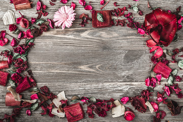 Upper, top, view from above, of decorative dried, painted flower petals, bark, in Christmas style, on a rustic, dark brown and white wooden background with free space for text writing