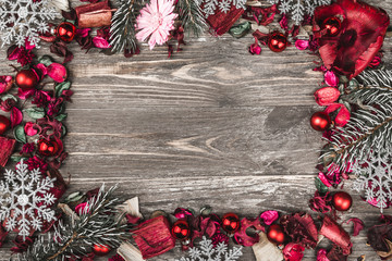Upper, top, view from above, of decorative dried, painted flower petals, bark, in Christmas style, homemade snowflakes and evergreen branch on a rustic background