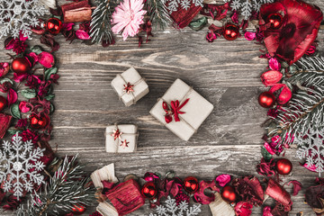 Upper, top, view from above, of decorative dried, painted flower petals, bark, in Christmas style, presents and evergreen branch on a rustic