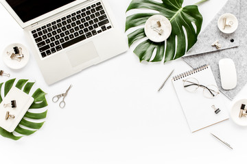 Home office workspace mockup with laptop, tropical leaves Monstera, clipboard, notebook and accessories on white background. Flat lay, top view