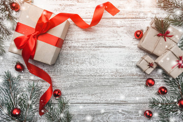 Christmas theme with fir branches, cones, present boxes and ribbon globes, on white wooden background viewed from above, in snow, greeting card with space for text