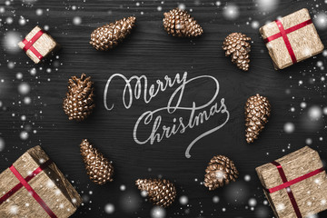 Circle from golden fir pines and gift, present boxes, Merry Christmas sign on snowy black, dark wooden background, with space for text xmas greeting card
